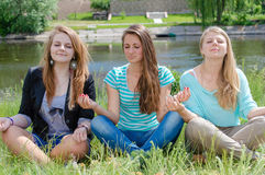 Three teen girls sitting in yoga position and meditating. Three teen friends girls sitting in meditation yoga position outdoors Stock Photos