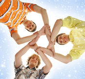 Three teenage boys holding in a form of a star. Three happy Caucasian teen boys in modern clothes holding together in a form of a star. The image is taken on a Royalty Free Stock Photo