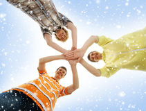 Three teenage boys holding in a form of a star. Three happy Caucasian teen boys in modern clothes holding together in a form of a star. The image is taken on a Stock Photography