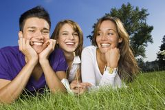 Three teenage friend lying down on the grass. Royalty Free Stock Image
