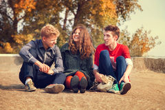 Three teenage friends have a fun time in golden autumn day Stock Images