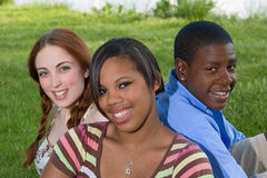 Three Teenage Friends Sitting in the Grass Stock Photo