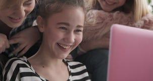 Teenage girls having fun reading social media content on laptop. Three teenage girl friends laughing while reading social media content on laptop stock footage