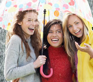 Three Teenage Girl Sheltering From Rain Beneath Umbrella. Smiling Royalty Free Stock Image