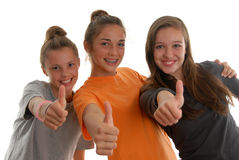 Three teenage girls all thumbs up smiling studio. Three teenage girls happy and smiling with thumbs up in approval of job well done, or everything is okay and Royalty Free Stock Photo