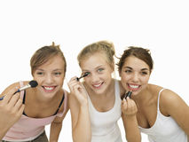 Three teenage girls applying make-up, smiling, front view, close-up, cut out Royalty Free Stock Image