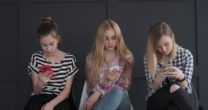 Three girls chatting using their mobile phones stock video footage