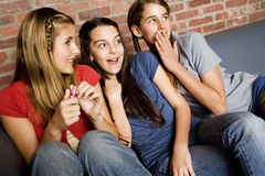 Three teenage girls giggling at something out of shot Royalty Free Stock Photography