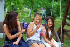 Three teenage girls having fun blowing bubbles Royalty Free Stock Images