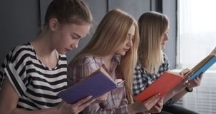 Teenage girls having fun while reading books. Three teenage girls having fun while reading books together at home stock video