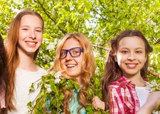 Three teenage girls holding benches of the tree Stock Image