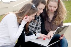 Three teenage girls with laptop Stock Photos