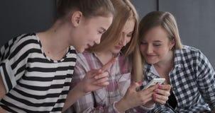 Teenage girls having fun watching media content on mobile phone. Three teenage girls laughing while watching media content on mobile phone stock footage