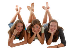 Three teenage girls laying on floor chin in hand. Three teenage girls laying on their stomach on the floor with chin in hands, and feet raised up and crossed Stock Image
