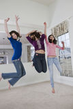 Three teenage girls leaping and dancing at home Royalty Free Stock Image