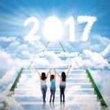 Three teenage girls looking at number 2017 Stock Photo