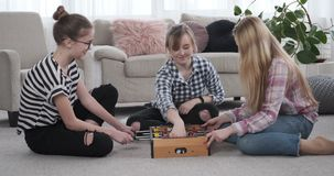 Three girls playing foosball at home. Three teenage girls playing foosball and celebrating success at home stock video footage