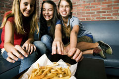 Three teenage girls sharing a plate of chips royalty free stock photos