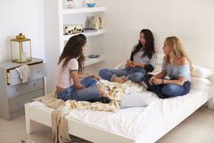 Three teenage girls sitting on bed with laptop talking Stock Photo