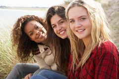 Three Teenage Girls Sitting In Sand Dunes Together. Outdoors Royalty Free Stock Photo