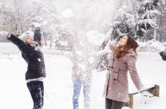Three teenage girls throwing snow in the air Stock Photography