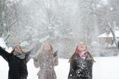 Three teenage girls throwing snow in the air Royalty Free Stock Images