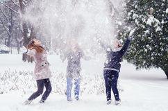Three teenage girls throwing snow in winter Royalty Free Stock Images