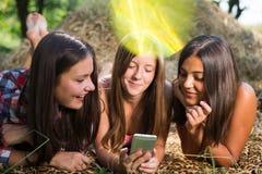 Three teenage girls using phone outdoors Royalty Free Stock Photography