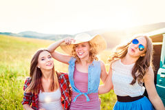 Three teenage hipster girls on a roadtrip, summer day Stock Photos