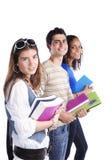 Three teenage studens. Three happy students holding books (isolated on white royalty free stock photos