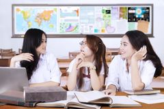 Three teenage students chatting in class Royalty Free Stock Image