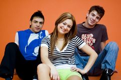 Three Teenagers. Two boys and a girl, teenagers, sitting on floor, orange background, smiling stock photography