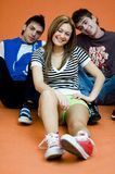 Three Teenagers. Two boys and a girl, sitting on floor smiling, girl slightly in front stock photography