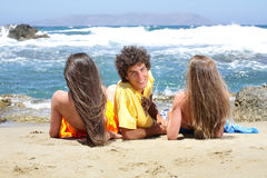 Three teenagers on the beach Stock Photos