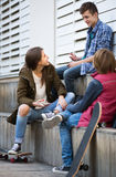 Three teenagers hanging out outdoors Stock Images