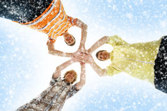 Three teenagers holding together on a snowy background. A group of three young and happy teenagers holding together. The image is taken on a light blue snowy Stock Photography