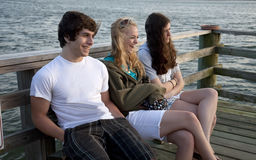 Three Teenagers Laughing. Three teenagers, one boy and two girls, sitting on a bench on a dock, laughing at something off camera Royalty Free Stock Photo