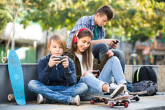 Three teenagers with phones outdoors Royalty Free Stock Image