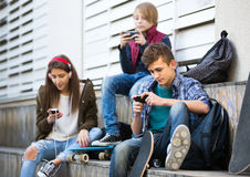 Three teenagers with phones outdoors Stock Images
