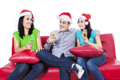 Three teenagers in santa hat drinking wine Royalty Free Stock Image