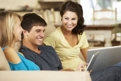 Three Teenagers  Sitting On Sofa At Home Using Tablet Computer And Laptop Stock Photography