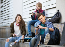 Three teenagers with smartphones in outdoors Stock Photos
