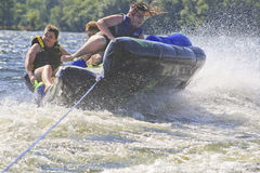 Three Teenagers on a Tube crashing Over a Wave Royalty Free Stock Photos