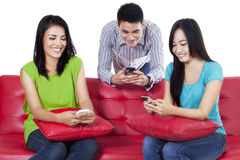 Three teenagers typing sms Royalty Free Stock Photography