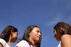 Three teenagers watching the sky. Three faces of women teenagerswatching the blue sky Stock Photo