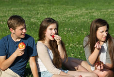 Three Teens Eating Fruit Stock Photography