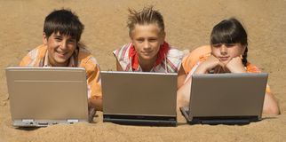 Three teens  with laptops Stock Photo