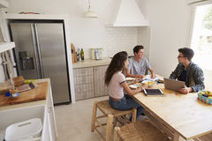 Three teens study in kitchen using computers, elevated view Stock Photos