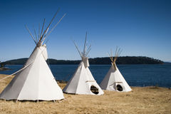 Three Teepees Together. Three teepees are lined up in a row in front of water. These teepees are used to provide shelter at a summer camp. Teepees were one form royalty free stock image