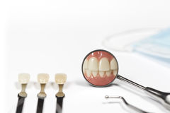 Three teeth next to dental mirror on white. Three teeth attached to metal rods next to dental pick and mirror displaying clenched front teeth besides mask on Stock Image